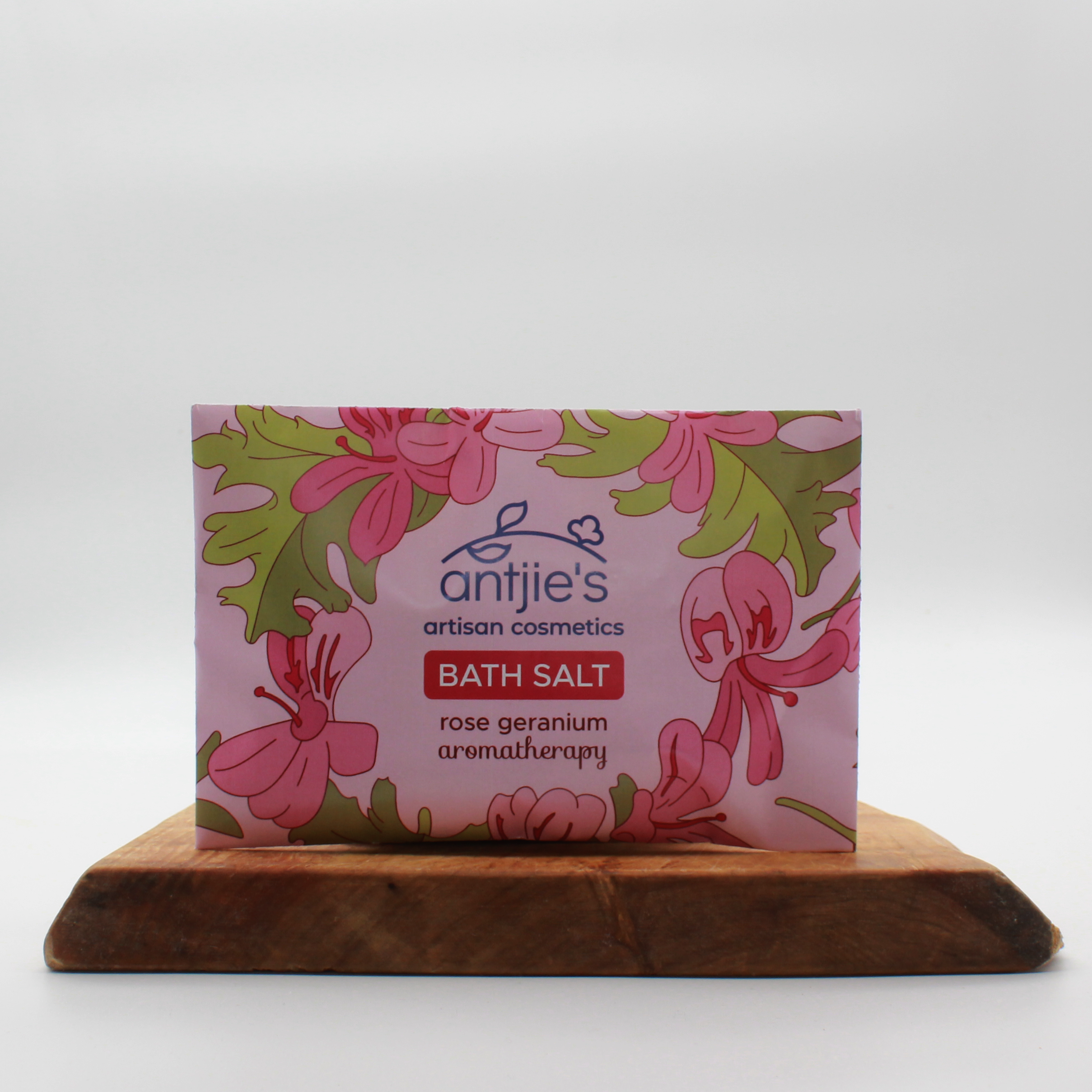 Rose geranium bath salts in an envelope sitting on a wooden board with a white background