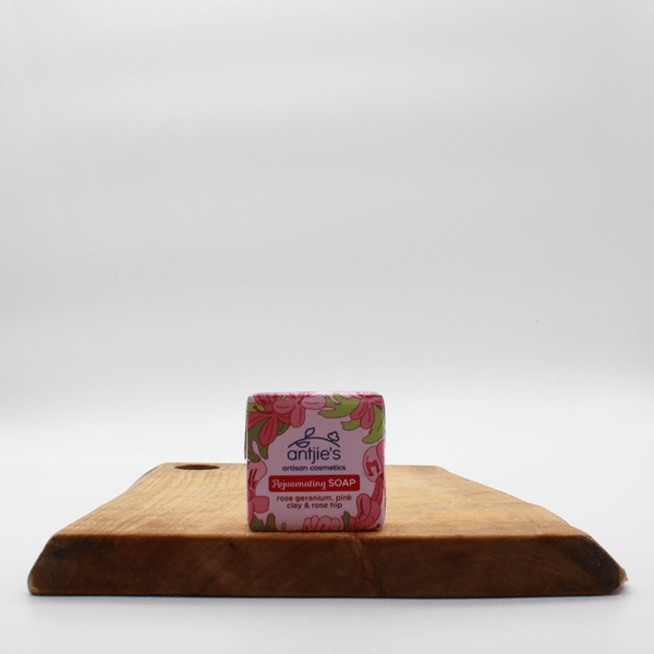 Rose Geranium, pink clay and rose hip soap in pink packaging sitting on a wooden board with a white background.