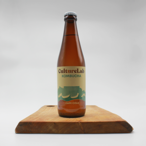 Cape Cola flavoured Kombucha by Culture Lab in a glass bottle sitting on a wooden board with a white background