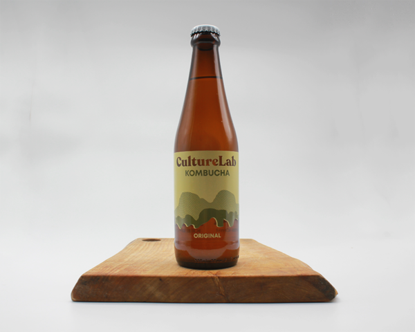Culture Lab Original kombucha in a glass bottle sitting on a wooden board with a white background