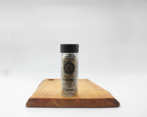 Rosemary Spice Jar in a glass bottle on a wooden board with a white background