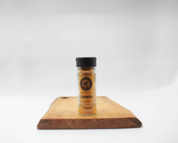turmeric spice in a glass jar sitting on a wooden board with a white background