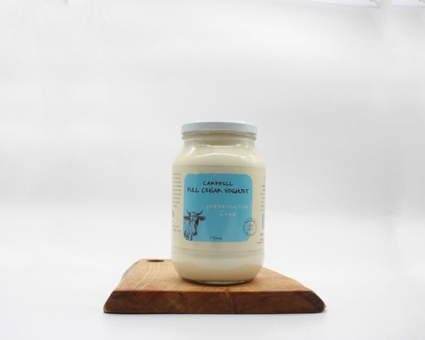 camphill full cream yogurt in a 1l glass jar sitting on a wooden bard with a white background