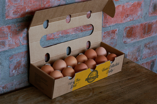 Free range eggs in cardboard box sitting on a wooden table