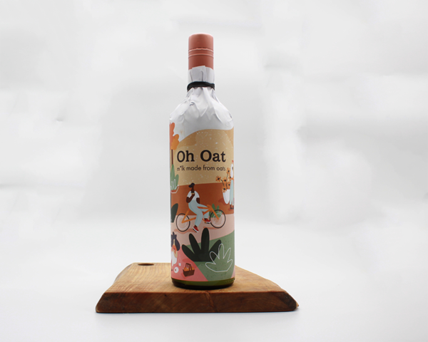 oat milk in recycled wine bottle wraped in paper sitting on a wooden board with a white background