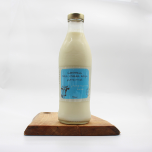 Camphill village full cream milk in a glass bottle sitting on a wooden board with a white background
